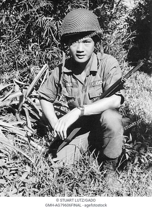 A photograph of an Army of the Republic of Vietnam soldier crouched with his rifle position across his lap, Vietnam, 1968
