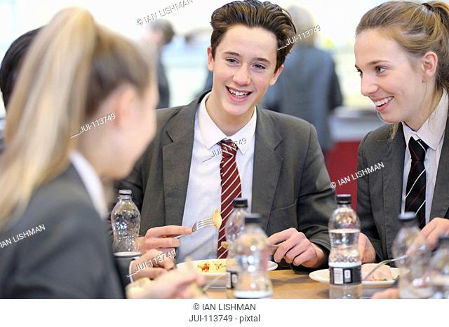 Smiling high school students eating lunch and talking in school cafeteria