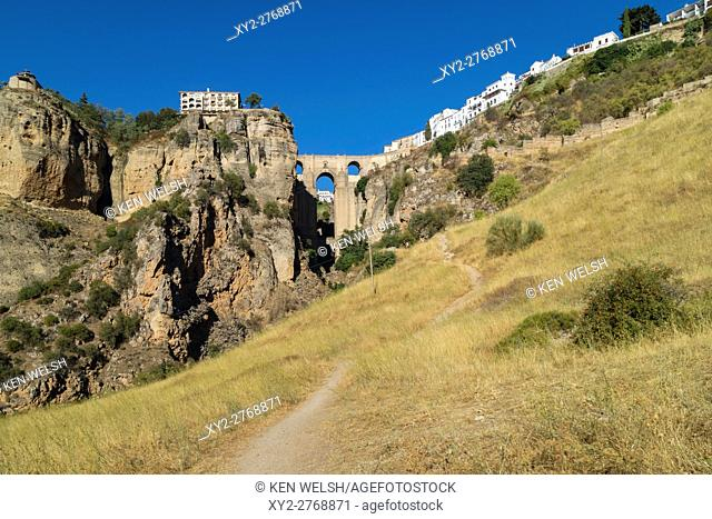 Ronda, Malaga Province, Andalusia, southern Spain. The town on both sides of the El Tajo gorge, seen from below. The bridge straddling the gorge is known as El...