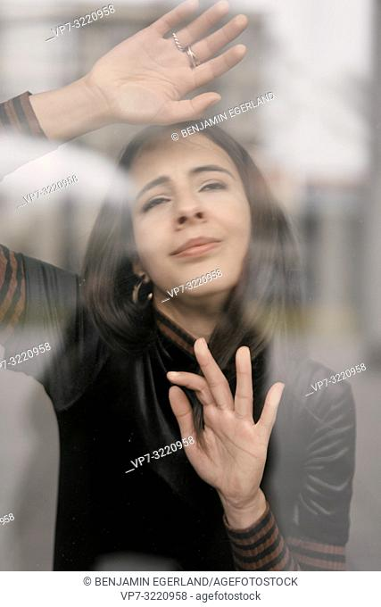 portrait of sensual woman behind glass window, missing, dreaming, in Munich, Germany