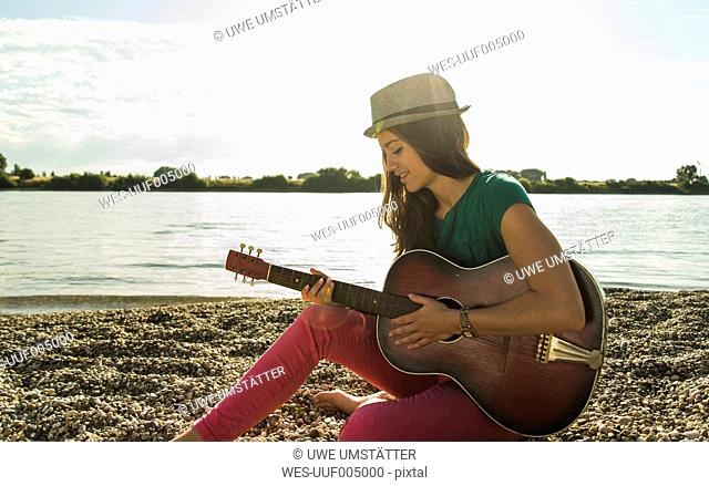 Young woman playing guitar by the riverside