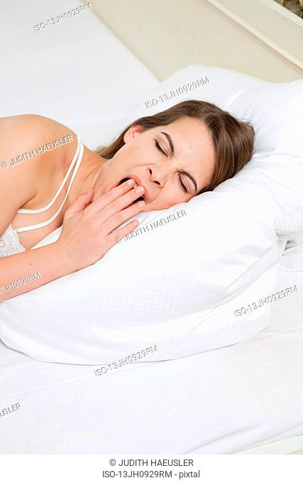 woman in bed yawning, close up