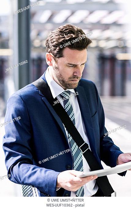 Businessman standing on parking level, reading on digital tablet