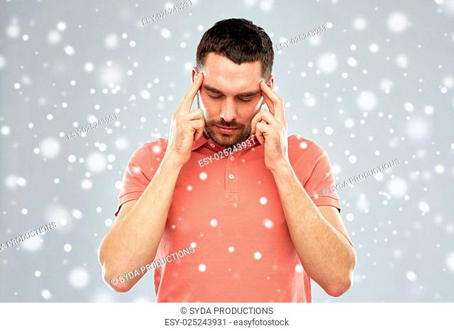people, emotions, winter, christmas and stress concept - man suffering from head ache or thinking over snow on gray background