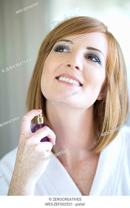 Smiling young woman applying fragrance