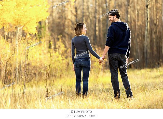 A young couple walking and enjoying each other's company in a city park in autumn; Edmonton, Alberta, Canada