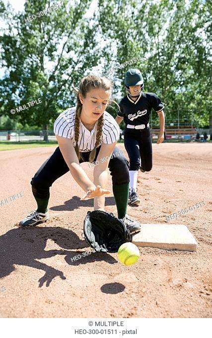 Middle school girl softball player catching softball at base