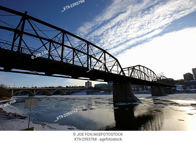 the old traffic bridge over the south saskatchewan river in winter flowing through downtown Saskatoon Saskatchewan Canada