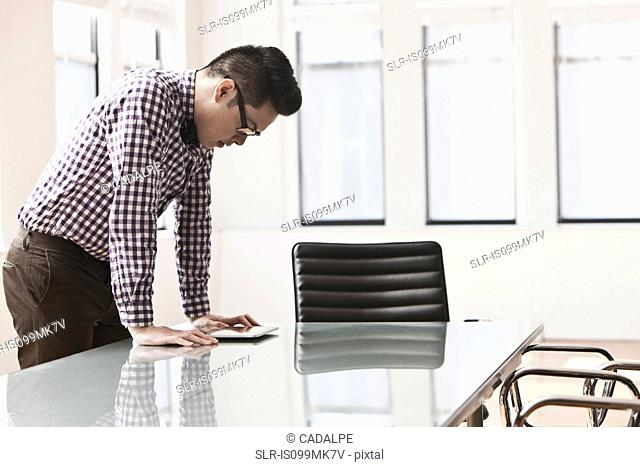 Young man looking at digital tablet on desk