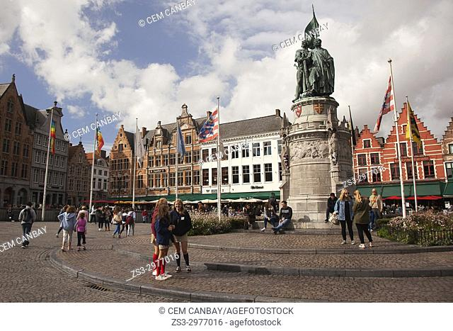 View to the statue and to the colorful buildings used as restaurants on the Market Square in the city center, Bruges, West Flanders, Belgium, Europe