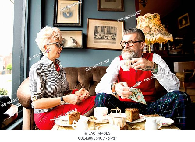 Quirky vintage couple drinking tea in tea room