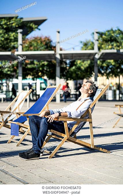 Mature man relaxing in deckchair on a square in the city