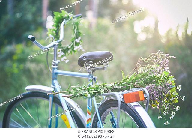 Flowers and garland on bicycle in garden