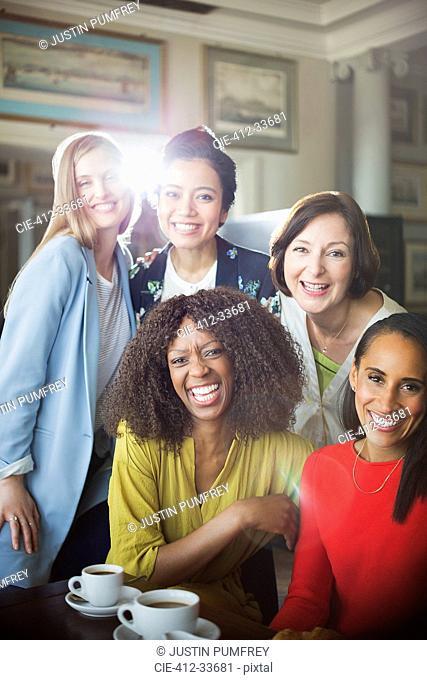 Portrait smiling women friends drinking coffee in restaurant