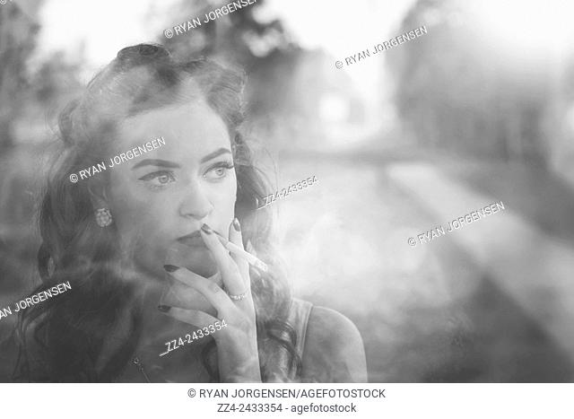 Outdoor black and white photo from 1920 of an elegant film noir lady smoking cigarette with vague expression on classic vintage street