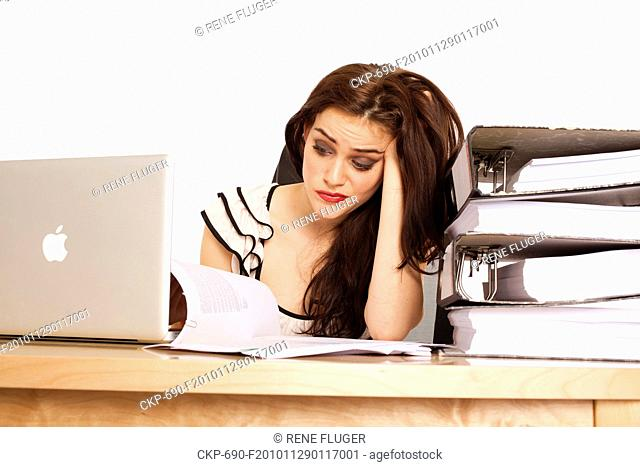 A beautiful young woman, lady, girl, secretary, personal assistant, office work, job, employee, worker, computer, notebook, MacBook Pro, paper work, folders