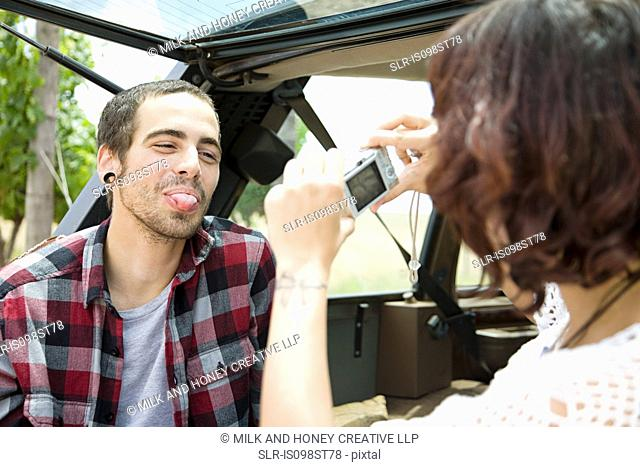 Woman taking picture of man sticking out tongue
