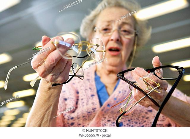 Low angle view of a confused senior woman holding glasses