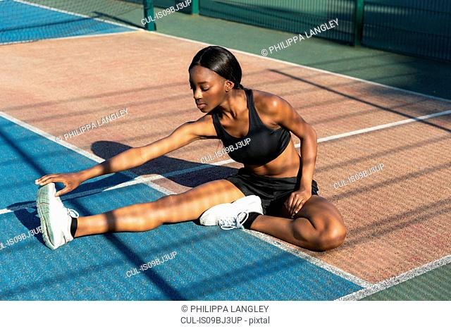 Young woman stretching in sports court