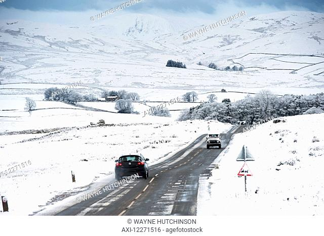 Traffic on the A683 between Kirkby Stephen and Sedbergh in snowy weather conditions; Cumbria, England