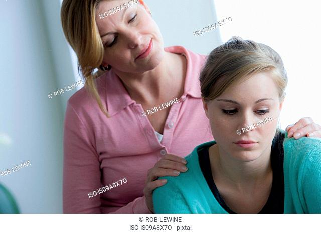 Mother comforting teenage daughter
