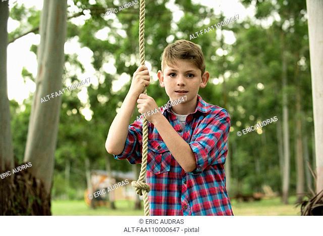 Boy on rope swing, portrait