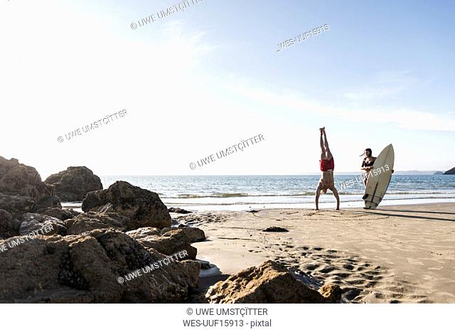 France, Brittany, young man doing a handstand and woman holding surfboard on the beach