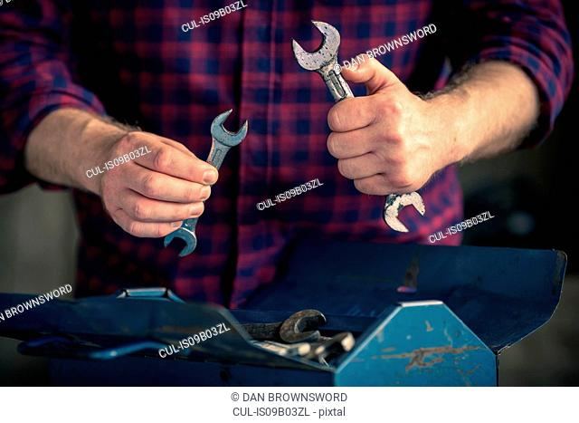 Man holding different sized spanners