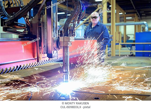 Worker operating plasma cutter to cut steel in engineering factory