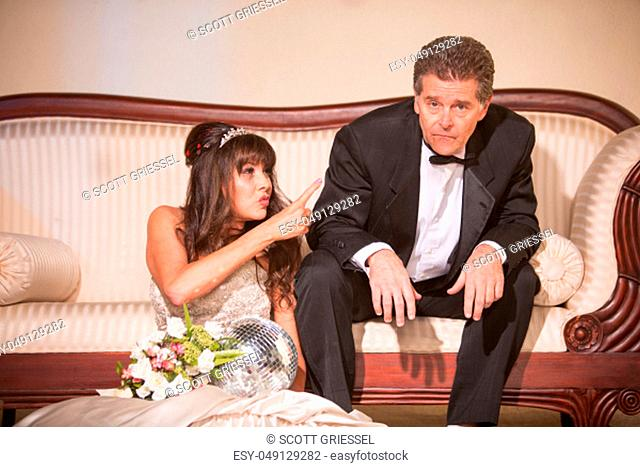 Upset bride pointing at new husband