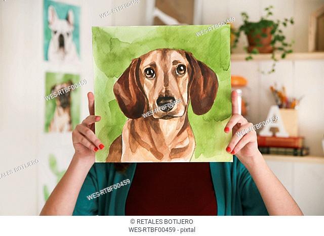 Artist hiding behind aquarelle of a dachshund