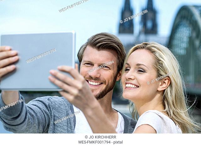 Germany, Cologne, portrait of smiling young couple taking a selfie with digital tablet