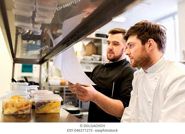 cooking food, profession and people concept - happy male chef and cook with grocery lists or bills at restaurant kitchen
