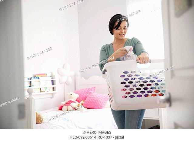 Woman with laundry basket in childs bedroom
