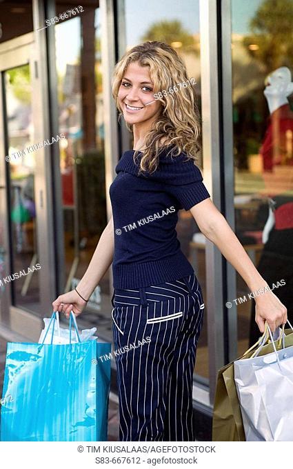Young girl walking down sidewalk with shopping bags