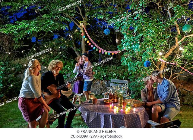 Three couples having fun at garden party at night