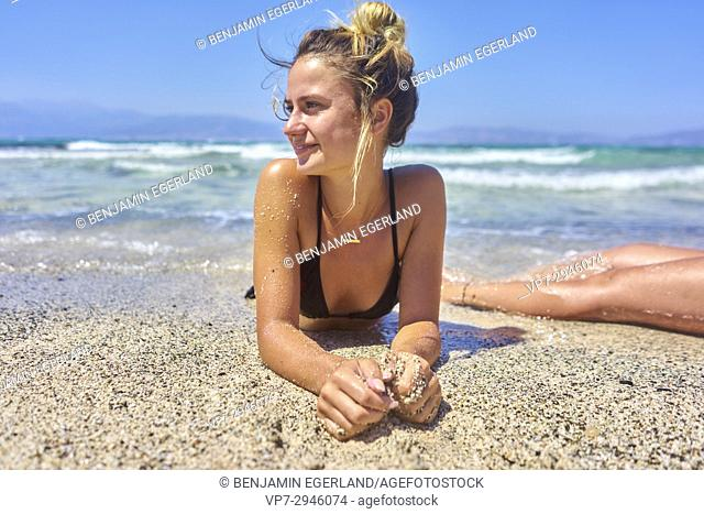 happy young woman enjoying laying at the beach. Dutch ethnicity. At holiday destination Chrissi Island, Crete, Greece