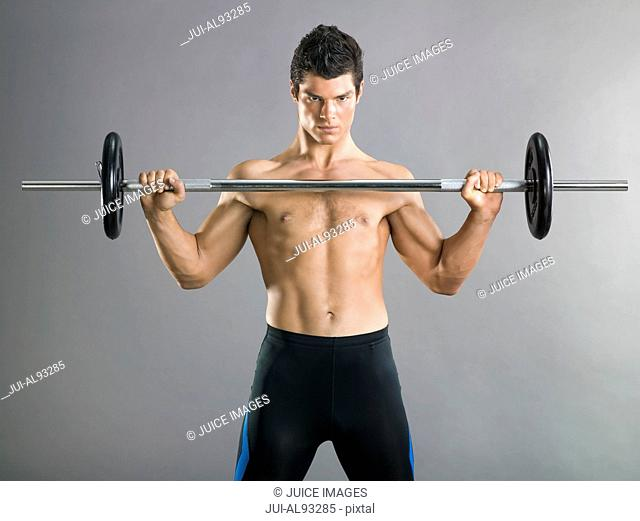 Bare-chested man lifting barbell