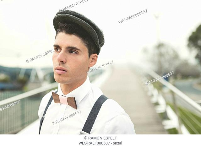 Portrait of young man wearing beret and a wooden bow tie