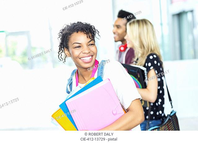Smiling university student carrying folders