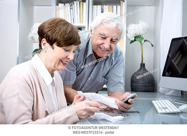 Senior couple with bills and calculator checking their expenses