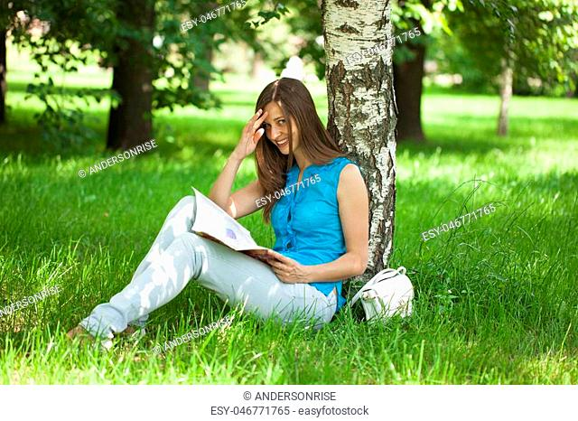 Young beautiful woman leafing through a magazine while sitting in the summer park