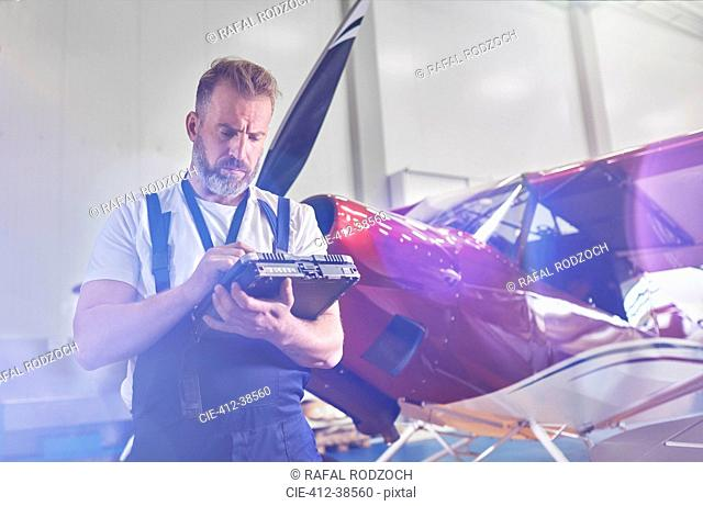 Male mechanic performing diagnostics with equipment near airplane in hangar