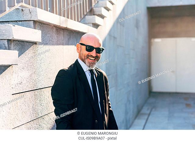 Portrait of mature businessman outdoors, standing beside steps, smiling