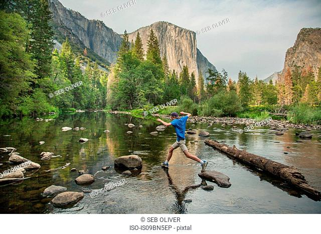 Tourist jumping across rocks in river, Yosemite National Park, California, USA