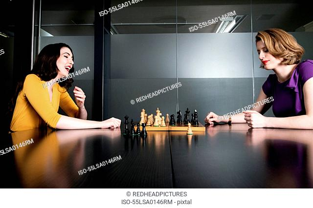 Two business executives playing chess in meeting room