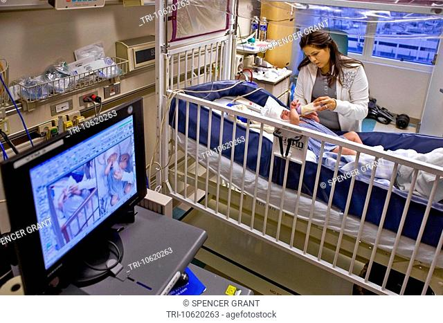 In a California hospital, a mother cares for her infant son suffering from spinal bifida. Note condition-monitoring EEG Electroencephalography Electrode Cap and...