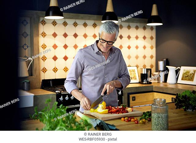 Smiling mature man chopping bell pepper in kitchen