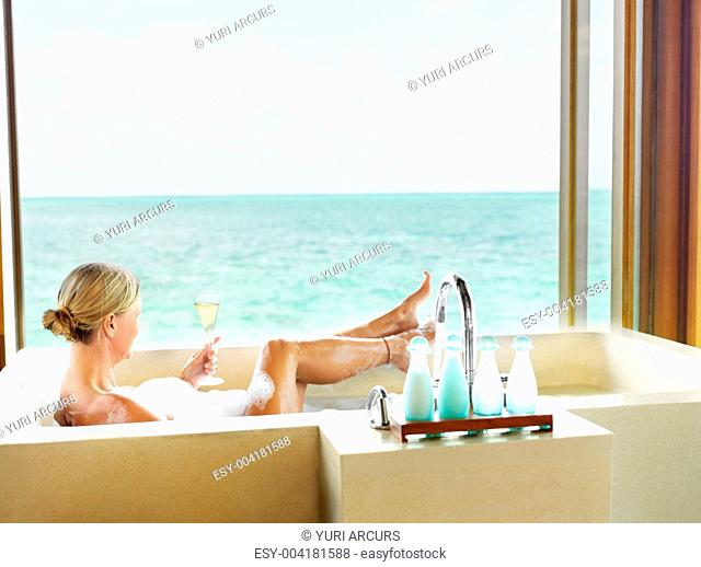 Mature lady in bathtub with a glass of cocktail at the a five star resort bathroom