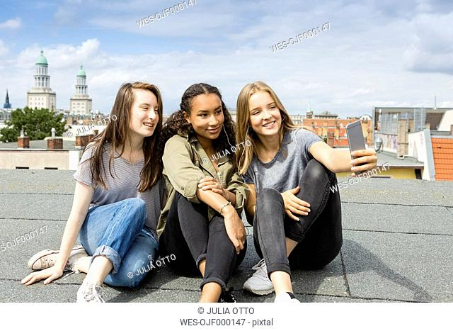 Germany, Berlin, three teenage girls sitting on roof top taking selfie with smartphone